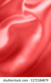 Coral satin fabric, draping with soft folds. Blurred background.