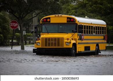 Coral Springs, Florida, USA - November 08, 2020: School Buses stuck in water during Hurricane Eta at Florida. Street Flood.