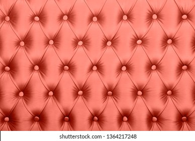Coral toned pink leather capitone textile background, retro Chesterfield style checkered soft tufted fabric furniture decoration with buttons, close up