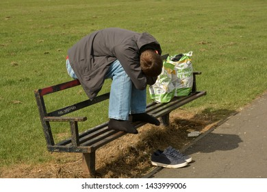 Corby, U.K., June 20 2019 - homeless man sleeping on a bench in England
