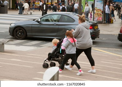 Corby, United Kingdom - august 28, 2018: Young mother walking in street with two childrens and pushchair. Active family