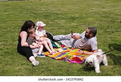 Corby, United Kingdom. June 01, 2018. Young family sitting in park on blanket. Father is taking a picture of his family. Summer holiday.