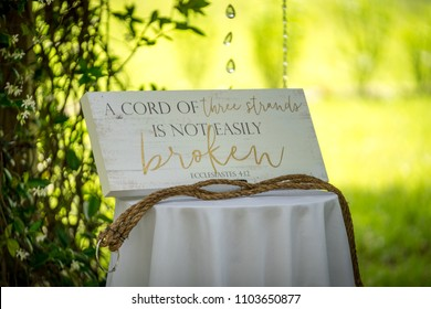 A cord of three strands is not easy broken sign at an outdoor wedding