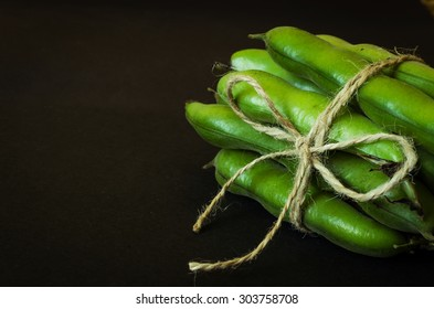 cord tied green bean pods on black background right position space for text