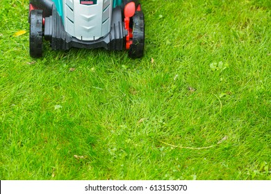 Cordless battery power lawn mower close up on green wet grass background. Full frame horizontal composition.