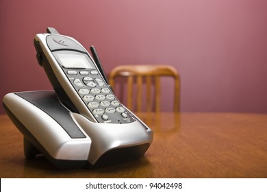 A cordless phone on a table with an out of focus chair