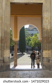 Cordoba, Andalusia / Spain - December 23 2016. The Mezquita.  A gateway to the complex. A young family in the entrance. The site is visited by both main faiths, Christian and Islamic.