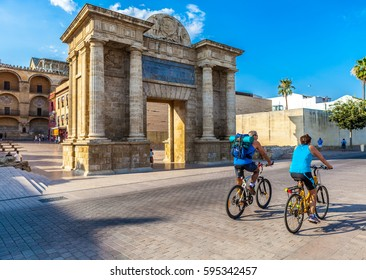 Cordoba, Andalusia, Spain. July 8,2016. Two cyclists are riding along Puerta del Puente Gate, Arch of triumph.