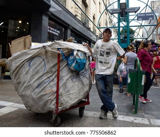 Cordoba, Argentina - 2017: A man collects cardboard for recycling on a pedestrian street at the city center