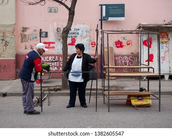 Cordoba City, Cordoba, Argentina - 2019: People prepare stands for a traditional flee market on the streets of the Guemes district.