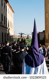 Cordoba, Spain - April 11, 2017: Easter nazarenes in white robes with purple hoods during procession holding big candle in Mosque of Cordoba, they are members of a brotherhood in the Holy Week