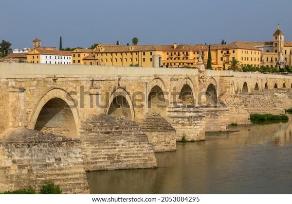 Cordoba, Spain - August 12, 2021:: People walk on the Roman Bridge of Cordoba, a stone bridge that spans river Guadalquivir