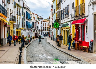 CORDOBA, SPAIN, JANUARY 8, 2016: people are walking through a narrow street of the spanish city cordoba, famous for the la mezquita cathedral.