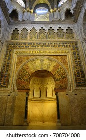 CORDOBA, SPAIN - JULY 18, 2015. Ornate mihrab in the Mezquita mosque of Cordoba, with paintings and inscriptions. The entire mihrab portal incorporates 1600kg of gold mosaic cubes.