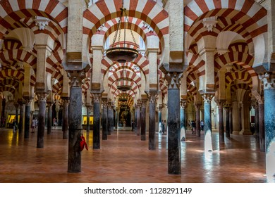 Cordoba, Spain - June 20, 2017: Pillars and arches with red and white stripes in the interior of Great Mosque of Cordoba and the Mezquita, Cathedral of Our Lady of the Assumption