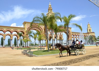 CORDOBA, SPAIN - MAY 22: Unidentified people ride a classic carriage in front of the facade of the Cordoba Fair on May 22, 2011 in Cordoba, Spain. Cordoba Fair includes carriages exhibitions