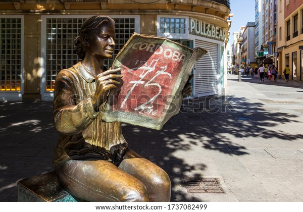 CORDOBA, SPAIN - MAY 30, 2019: Street view with La Lectora, bronze statue of a woman reading Diario Cordoba or Cordoba Newspaper, monument to the 75th anniversary of the newspaper by Marco Augusto