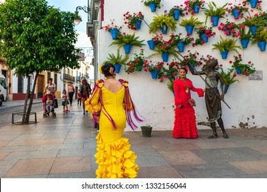 Cordoba, Spain - May 8 2018: Spanish women wearing traditional flamenco dresses taking photos during Patios Festival in Cordoba.