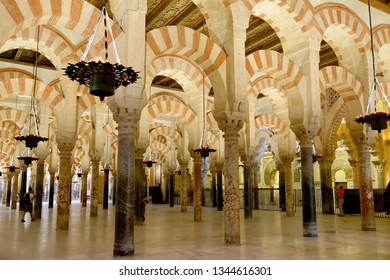 CORDOBA, SPAIN - SEPTEMBER 1, 17: Pillars and arches with red and white stripes in the interior of Mezquita - the Great Mosque of Cordoba, Cathedral of Our Lady of the Assumption. Mihrab at right side