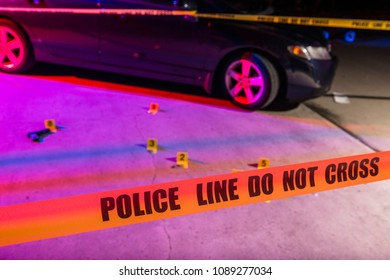 Cordon tape, marking a police line, is stretched in front of a crime scene.