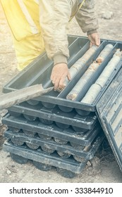 Core drill worker extracts core samples from a drill pipe in plastic boxes. Made with shallow dof and vintage style.