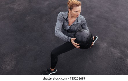 Core strength and stability workout. Fit young woman exercising outdoors with medicine ball. Fitness woman working out at outdoor gym.