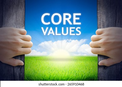 Core Values. Hands opening a wooden door then found a texts floating among new world as green grass field, Blue sky and the Sunrise.