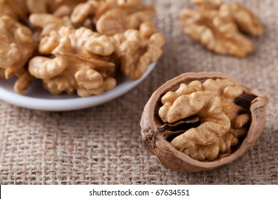 Cores of matured nuts in plate and cracked brown Circassian walnut close-up on the sackcloth background