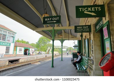 CORFE CASTLE, UK - MAY 21, 2018: The platforms at Corfe Castle railway station with the station Master waiting for the arrival of an heritage steam train
