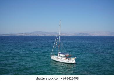 Corfu, Greece - AUGUST 02, 2017: White sailboat in the sea of Notio Steno Kerkiras