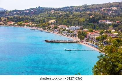 Corfu, Greece -August 17, 2015: Beautiful beach in Ipsos on Corfu, tourists enjoying a nice summer day at the beach. Kerkyra (Corfu), Greece