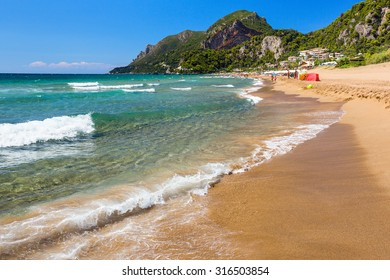 Corfu, Greece -August 21, 2015: Beautiful Glyfada beach on Corfu, tourists enjoying a nice summer day at the beach. Kerkyra (Corfu), Greece