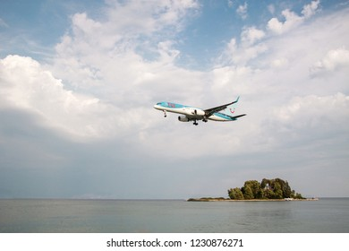 Corfu, Greece - August, 24 2018: the plane Boeing 757-200 of Tuifly Belgium flying over Mouse island and the sea on Corfu, Greece. Space for text. Passenger jet plane.
