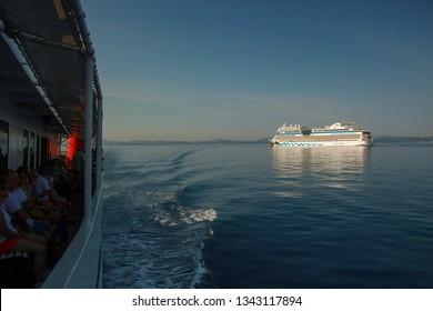 Corfu, Greece - August 24 2018: Big white luxury cruise ship AIDA blu in the Ionian sea near island Corfu. German line AIDA Cruises. Beautiful seascape. Space for text. Background with cruise liner.