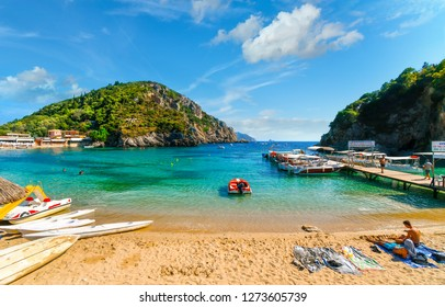 Corfu, Greece - September 16 2018: Tourists relax in the clear waters and on the sandy Palaiokastritsa beach and bay near the boat dock on the Aegean island of Corfu, Greece.