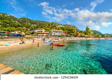 Corfu, Greece - September 16 2018: Tourists relax in the clear turquoise waters and on the sandy Palaiokastritsa beach on the Aegean island of Corfu, Greece.