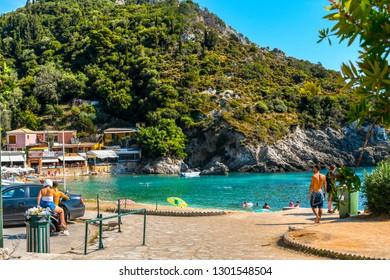 Corfu, Greece - September 16 2018: A young couple on a motorcycle arrive at a small bay near Palaiokastritsa Beach on the Greek island of Corfu.