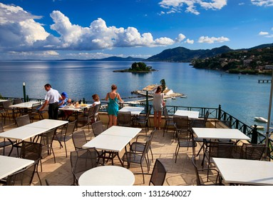 Corfu, Greece, September 3, 2014. People on the veranda in the cafe and a beautiful view of the coast of Corfu island