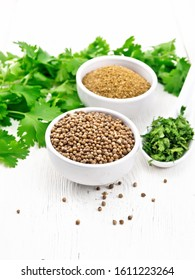 Coriander seeds and ground in two bowls, dried cilantro in a spoon, seasoning greens on wooden board background