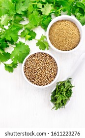 Coriander seeds and ground in two bowls, dried cilantro in a spoon, seasoning greens on wooden board background from above