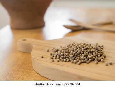 Coriander seeds on wooden board. Preparation ingredient for cooking.