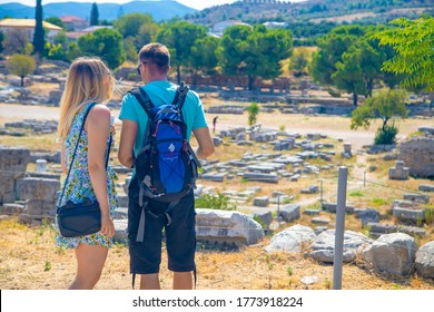 Corinth .Greece- August 30. 2019; A young couple of tourists on the ruins of the temple of Apollo in Corinth