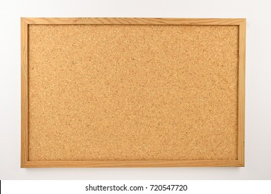 Cork board with a wooden frame against a white background