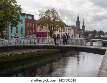 Cork City, Ireland - 18th June, 2019: Tourists on a pedestrian bridge enjoying the view over the river Lee in Cork city centre
