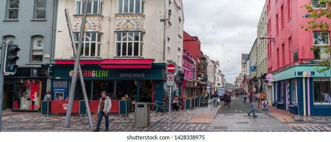 Cork City, Ireland - 18th June, 2019: Street view of Oliver Plunkett Street and Grand Parade in Cork city centre,  Oliver Plunkett Street is a well known shopping street in Cork city, Ireland