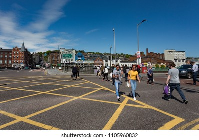 Cork City, Ireland - 18th May, 2018: People crossing the street on Merchant's Quay across from St Patricks bridge in Cork city centre on a sunny spring afternoon