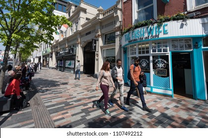 Cork City, Ireland - 18th May, 2018: People walking the streets of Grand Parade outside the English market in Cork city centre.