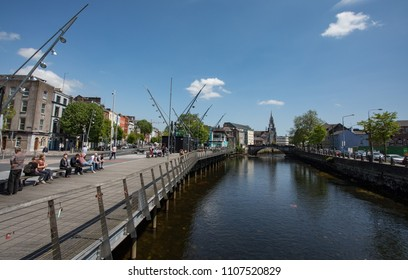 Cork City, Ireland - 18th May, 2018: People relaxing and enjoying the sunshine on the boardwalk of the river Lee in Cork city centre, Ireland