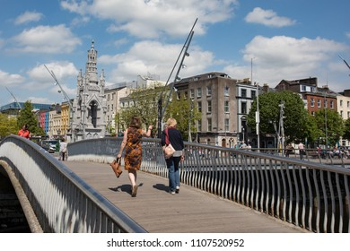 Cork City, Ireland - 18th May, 2018:two women crossing pedestrian footbridge over the river Lee towards grand parade in Cork city centre, Ireland