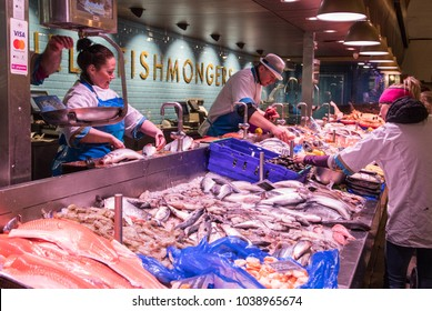 Cork City, Ireland - 24th February  2018: Fishmongers preparing fish at the English market in Cork City,The Market open since 1788 is a well know local market popular with locals and tourists.